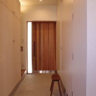 片開きドア北欧スタイルのおしゃれな玄関ホール (白い壁、コンクリートの床、木目調のドア、グレーの床) の写真
