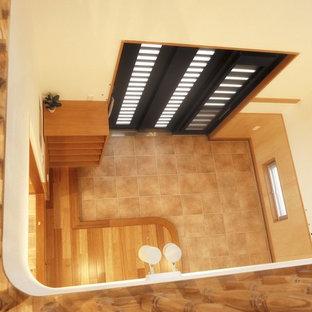 На фото: узкие прихожие в восточном стиле с полом из керамической плитки, раздвижной входной дверью, черной входной дверью и бирюзовым полом