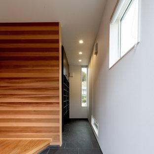 Aménagement d'une grand entrée avec un mur blanc, un sol en carrelage de porcelaine, une porte simple, une porte en bois brun, un sol noir, un plafond en papier peint, du papier peint et un couloir.