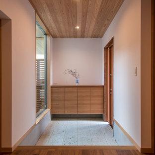 他の地域の片開きドアアジアンスタイルのおしゃれな玄関ホール (白い壁、木目調のドア、グレーの床) の写真