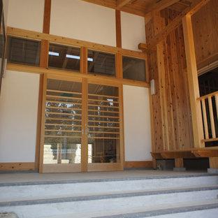 Idéer för en stor klassisk entré, med vita väggar, betonggolv, en skjutdörr, mellanmörk trädörr och grått golv