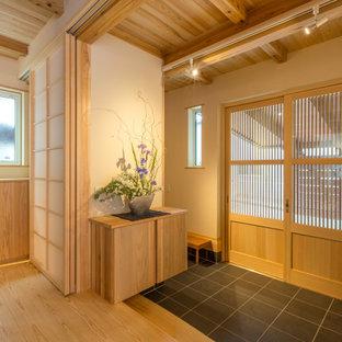 他の地域の中くらいの引き戸アジアンスタイルのおしゃれなマッドルーム (木目調のドア、黒い床、ベージュの壁) の写真