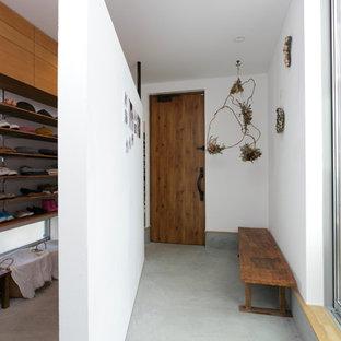 他の地域の片開きドアコンテンポラリースタイルの玄関の画像 (茶色い壁、コンクリートの床、木目調のドア、グレーの床)