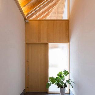 他の地域の片開きドア和風のおしゃれな玄関ホール (白い壁、コンクリートの床、淡色木目調のドア、グレーの床) の写真