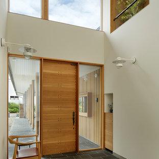 他の地域の片開きドアコンテンポラリースタイルのおしゃれな玄関ホール (白い壁、木目調のドア、黒い床) の写真
