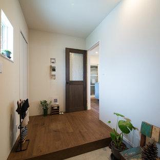 他の地域の片開きドアラスティックスタイルのおしゃれな玄関 (白い壁、木目調のドア、コンクリートの床、グレーの床) の写真