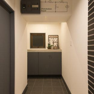 他の地域のインダストリアルスタイルのおしゃれな玄関ホール (白い壁、磁器タイルの床、黒い床、下駄箱) の写真
