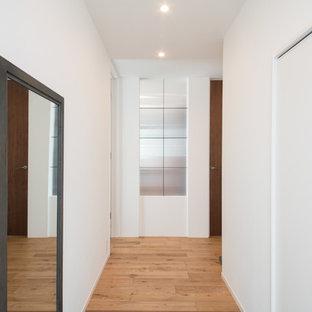 Cette image montre une entrée minimaliste avec un mur blanc, un sol de tatami et un sol gris.