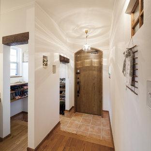 Inspiration för en orientalisk hall, med vita väggar, klinkergolv i terrakotta, en enkeldörr, mellanmörk trädörr och orange golv