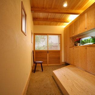 他の地域の中くらいの引き戸和風のおしゃれな玄関ホール (白い壁、淡色木目調のドア、グレーの床) の写真
