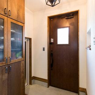 他の地域の小さい片開きドアコンテンポラリースタイルのおしゃれな玄関 (白い壁、コンクリートの床、濃色木目調のドア、グレーの床) の写真