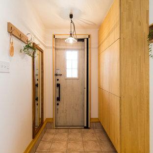他の地域の片開きドアラスティックスタイルのおしゃれな玄関 (白い壁、白いドア、グレーの床) の写真