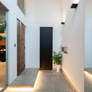 福岡の片開きドアモダンスタイルのおしゃれな玄関ホール (白い壁、磁器タイルの床、木目調のドア、クロスの天井、壁紙) の写真