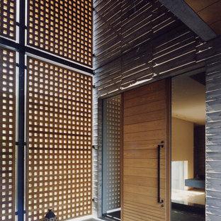 Bild på en orientalisk ingång och ytterdörr, med en pivotdörr, mellanmörk trädörr, grå väggar och grått golv