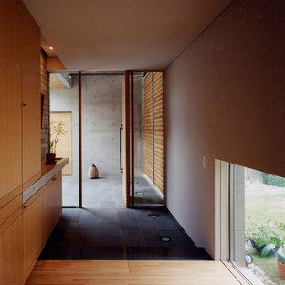 На фото: узкая прихожая в восточном стиле с поворотной входной дверью, входной дверью из дерева среднего тона, белыми стенами и серым полом с
