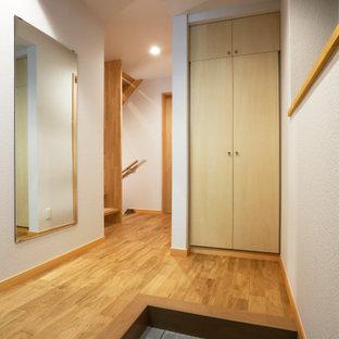 東京23区の小さい片開きドアモダンスタイルのおしゃれな玄関ホール (白い壁、淡色無垢フローリング、青いドア、クロスの天井、壁紙) の写真