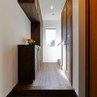 他の地域の片開きドアミッドセンチュリースタイルのおしゃれな玄関 (白い壁、木目調のドア、グレーの床) の写真