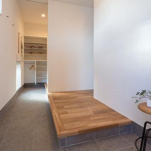 Immagine di un ingresso o corridoio minimal con pareti bianche e pavimento grigio