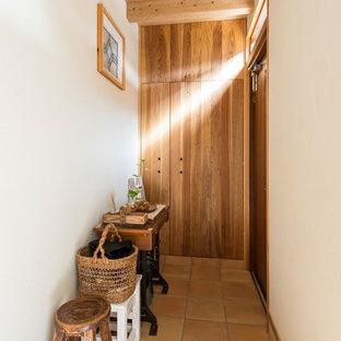 Foto de hall de estilo zen, pequeño, con paredes blancas, puerta de madera en tonos medios y suelo de baldosas de terracota