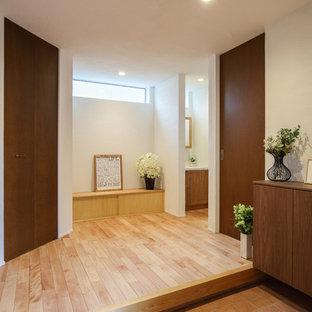他の地域の中くらいの引き戸モダンスタイルのおしゃれな玄関ホール (白い壁、磁器タイルの床、木目調のドア、オレンジの床) の写真