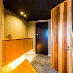 名古屋の片開きドアアジアンスタイルのおしゃれな玄関ホール (茶色い壁、コンクリートの床、黒いドア、グレーの床) の写真