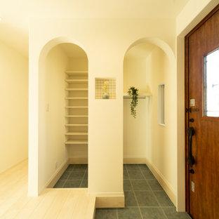 Пример оригинального дизайна: узкая прихожая в стиле шебби-шик с белыми стенами, полом из фанеры, одностворчатой входной дверью, входной дверью из темного дерева, белым полом, потолком с обоями и обоями на стенах