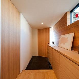 他の地域の中くらいの片開きドアモダンスタイルのおしゃれな玄関ホール (白い壁、木目調のドア、黒い床) の写真
