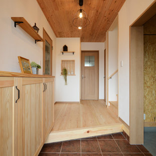 他の地域のカントリー風おしゃれな玄関 (白い壁、茶色い床) の写真