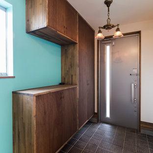 Exempel på en liten asiatisk hall, med blå väggar, mellanmörkt trägolv, en skjutdörr, metalldörr och beiget golv