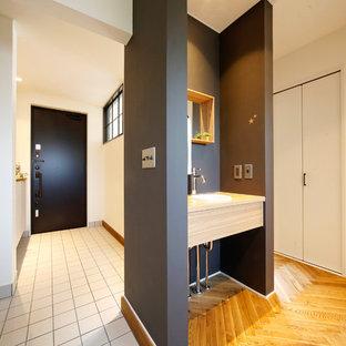 札幌の片開きドアトランジショナルスタイルのおしゃれな玄関ホール (白い壁、黒いドア、白い床) の写真