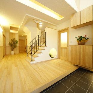他の地域の大きい両開きドアモダンスタイルのおしゃれな玄関ホール (白い壁、淡色無垢フローリング、茶色いドア、ベージュの床) の写真
