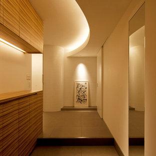 大阪の広いモダンスタイルのおしゃれな玄関ホール (白い壁、セラミックタイルの床、グレーの床) の写真