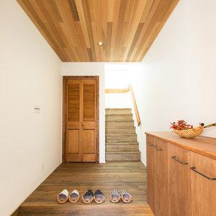 他の地域のおしゃれな玄関 (白い壁、茶色い床) の写真