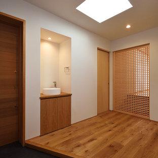 他の地域の引き戸和風のおしゃれな玄関ドア (茶色い壁、コンクリートの床、木目調のドア、グレーの床) の写真