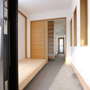 Exemple d'une entrée asiatique avec un mur blanc, un sol en bois clair, une porte coulissante, une porte noire et un sol beige.