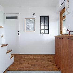神戸の中くらいの片開きドアインダストリアルスタイルのおしゃれな玄関ホール (白い壁、無垢フローリング、白いドア、グレーの床) の写真