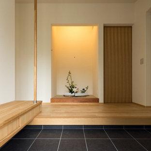 他の地域の中サイズの引き戸和風のおしゃれな玄関ホール (白い壁、磁器タイルの床、黒いドア、グレーの床) の写真