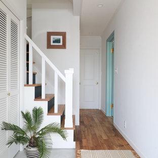 他の地域のビーチスタイルのおしゃれな玄関 (白い壁、コンクリートの床、グレーの床) の写真