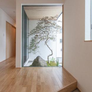 他の地域の片開きドアモダンスタイルのおしゃれな玄関 (白い壁、木目調のドア、グレーの床) の写真