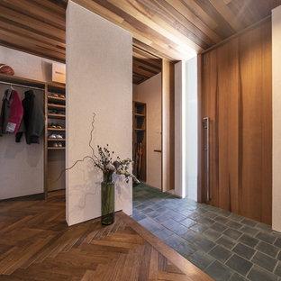 他の地域の広い片開きドアミッドセンチュリースタイルのおしゃれな玄関ホール (白い壁、木目調のドア、黒い床) の写真