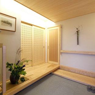 Пример оригинального дизайна интерьера: маленькая узкая прихожая в восточном стиле с гранитным полом, раздвижной входной дверью, входной дверью из светлого дерева, бежевыми стенами и серым полом