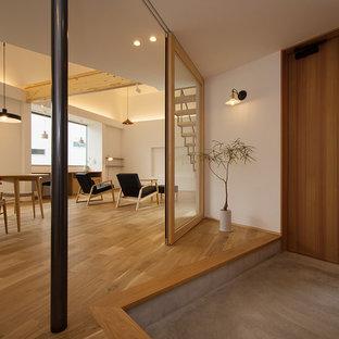 他の地域の片開きドア北欧スタイルのおしゃれな玄関ホール (白い壁、コンクリートの床、木目調のドア、グレーの床) の写真