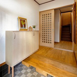 他の地域の北欧スタイルのおしゃれな玄関ホール (マルチカラーの壁) の写真