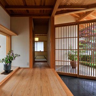 Идея дизайна: прихожая в восточном стиле с белыми стенами, раздвижной входной дверью, паркетным полом среднего тона и коричневым полом
