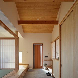 他の地域の片開きドア和風のおしゃれな玄関 (白い壁、コンクリートの床、木目調のドア、グレーの床) の写真