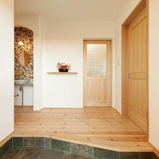 他の地域のエクレクティックスタイルのおしゃれな玄関ホール (白い壁、グレーの床) の写真