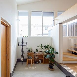 他の地域の大きい片開きドアコンテンポラリースタイルのおしゃれな玄関ラウンジ (白い壁、コンクリートの床、淡色木目調のドア、グレーの床) の写真