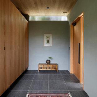 他の地域の片開きドアアジアンスタイルのおしゃれな玄関ホール (グレーの壁、木目調のドア、グレーの床) の写真