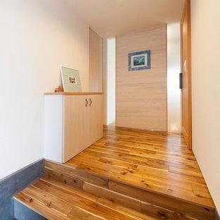 他の地域の中くらいのコンテンポラリースタイルのおしゃれな玄関ホール (白い壁、無垢フローリング、茶色い床) の写真