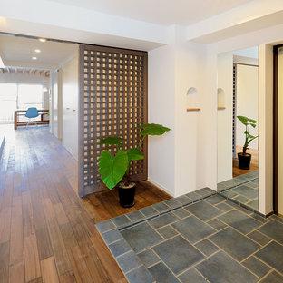 東京23区の片開きドアモダンスタイルのおしゃれな玄関ホール (白い壁、白いドア、グレーの床) の写真